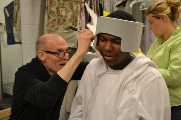 Left to right, Professor Dean Mogle fits 'Magic Flute' ensemble member Brandon Bell for a mask, assisted by Crafts & Masks Artisan Amanda Kai Newman.