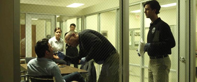 CCM alumnus Cooper Thornton as Dr. Benson, leaning over Ben Affleck in the film 'Gone Girl.'