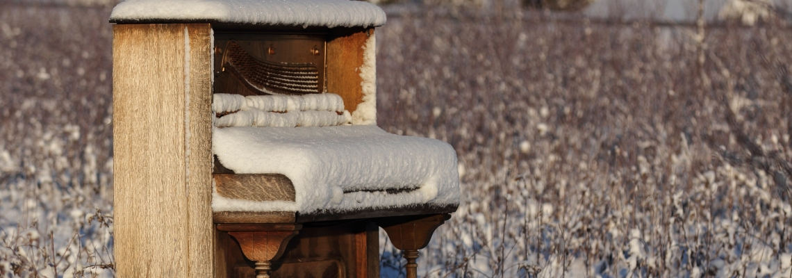 Upright piano that has been abandoned in a snowy winter field / meadow.