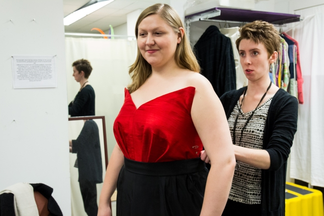 Maria Lenn built and draped this dashing red and black dress for Jessica Faselt (playing Hanna Glawari on Friday and Sunday) from Greta Stokes' designs. Lenn is fitting Faselt while Stokes and her assistant, Sarah Red Redden look on as Stokes' designs come to life. Photography by Steve Shin.