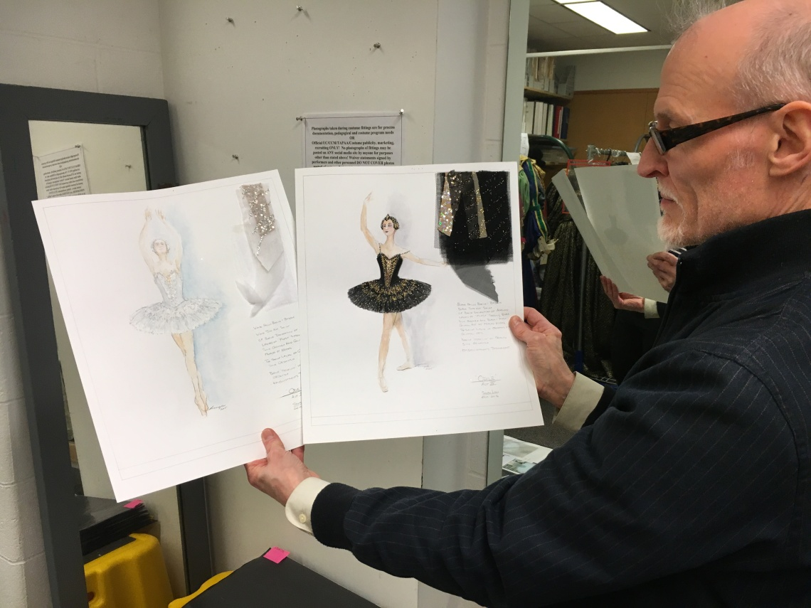 Dean Mogle holds the white and black swan design sketches for CCM's production of Swan Lake.