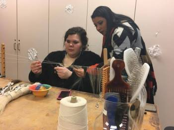 """Danae Jimenez with fellow wig and make-up student Meredith Keister as she """"wefts,"""" or creates tracks of hair, for a wig."""