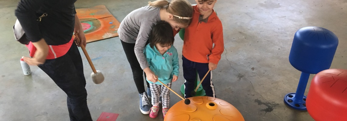 Children playing on tank drums made of repurposed propane tanks, which will be installed at Percussion Park.