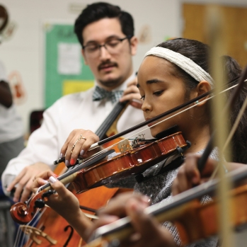 A teacher instructs young students on stringed instruments.