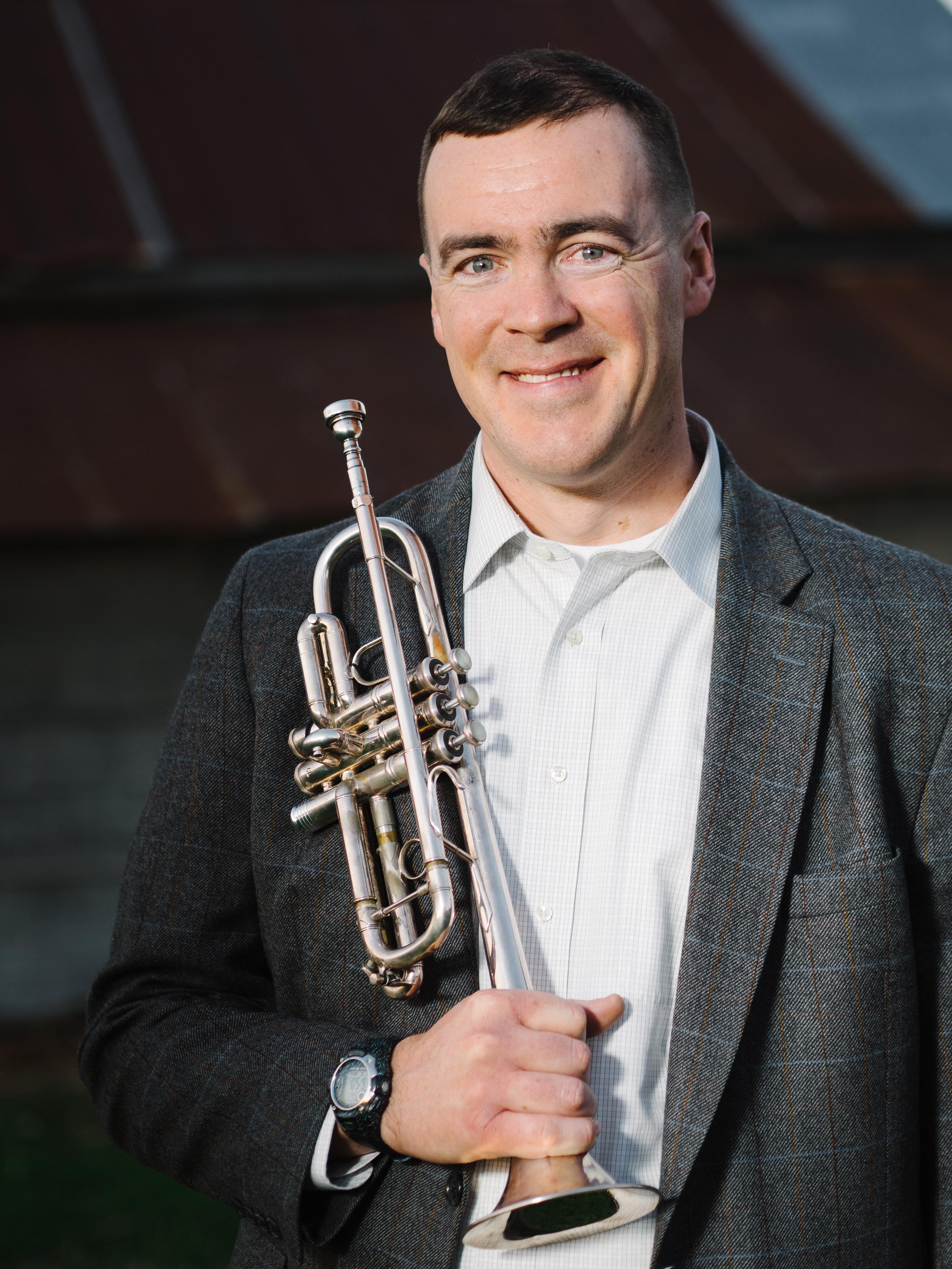 A portrait of new CCM faculty member Michael Mergen holding a trumpet.
