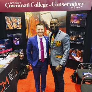 Kevin Michael Holzman and Omar Thomas in front of CCM's booth at the Midwest Clinic International Band and Orchestra Conference in Chicago in December 2019.